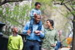 A New York city park in the spring. A family, parents and two boys.  A child riding on his father's shoulders.